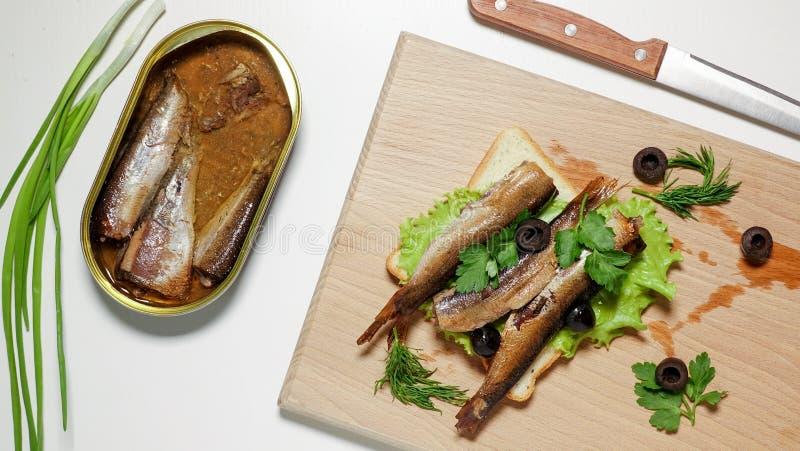 Sandwich avec des sardines, des esprots, des oignons et des olives sur un conseil image libre de droits