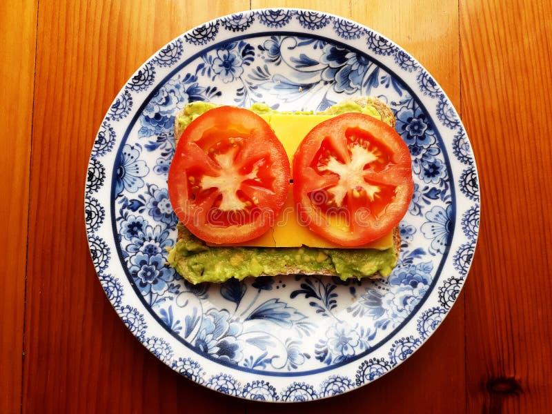 Sandwich avec l'avocat, le fromage et les tomates du plat image libre de droits