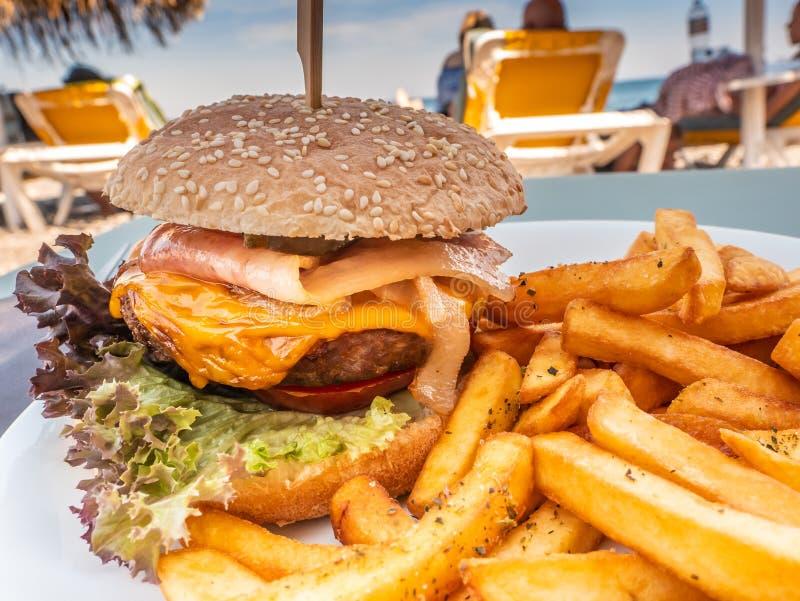 Sandwich avec l'hamburger chevronné même de viande dans un plat avec des pommes frites image stock
