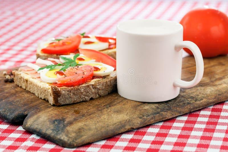 Sandwich avec l'oeuf, le jambon et la tomate images stock