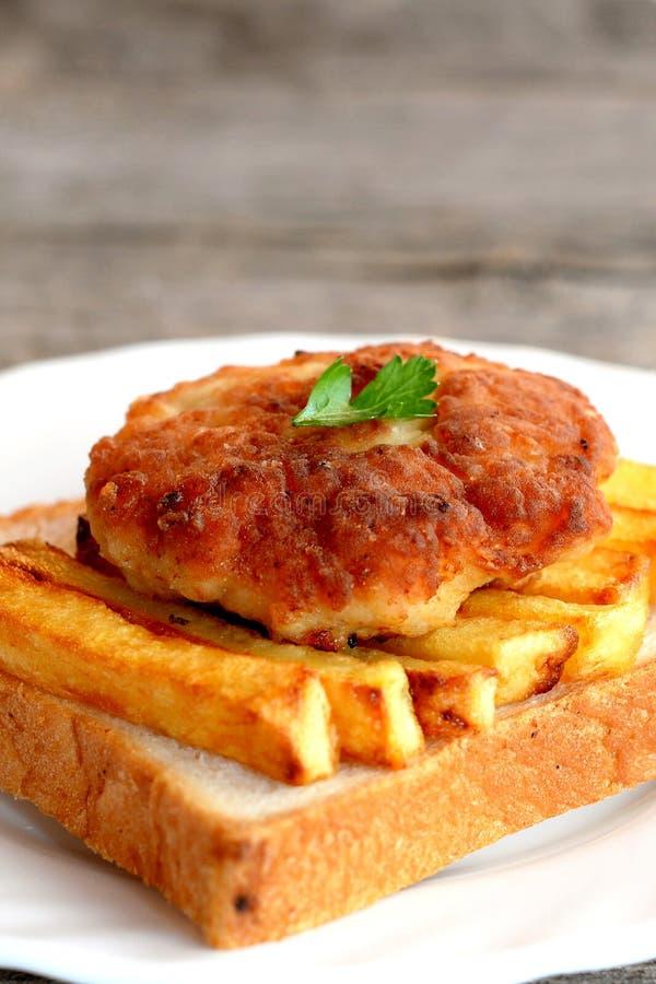 Sandwich avec la côtelette frite de pommes de terre et de viande de la Turquie d'un plat et sur la vieille table en bois closeup photographie stock