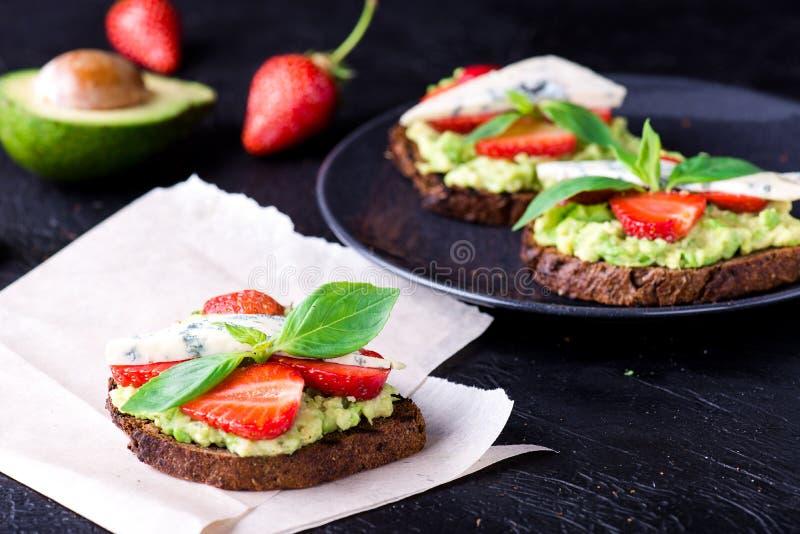 Sandwich avec la fraise sur le livre blanc images stock