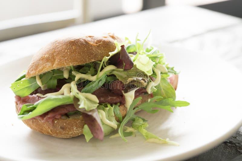 Sandwich avec le carpaccio, le salade et la sauce de boeuf sur plate-1 blanc images stock