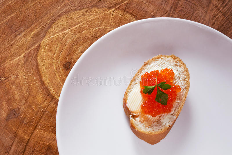 Sandwich avec le caviar rouge saumoné du plat blanc image stock