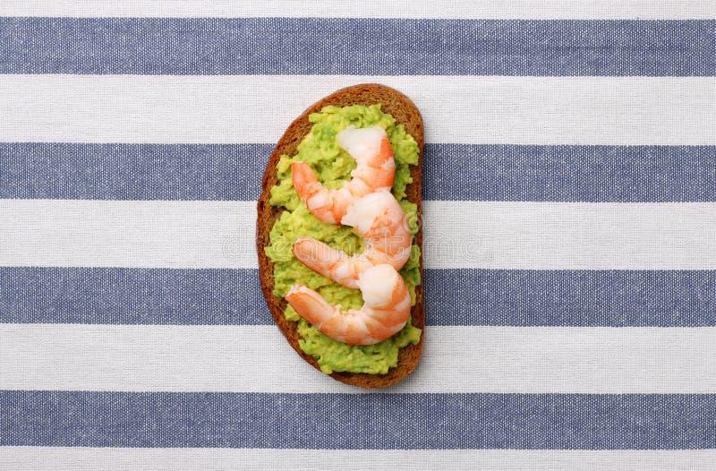 Sandwich avec le guacomole d'avocat et srimp de fruits de mer sur le fond clair image stock
