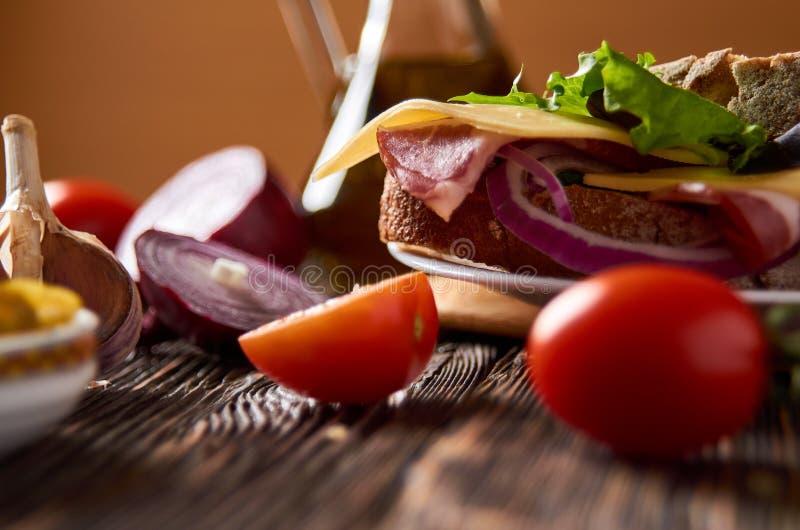 Sandwich avec le lard, le fromage, l'ail, le poivre de jalapeno et les herbes d'un plat image stock