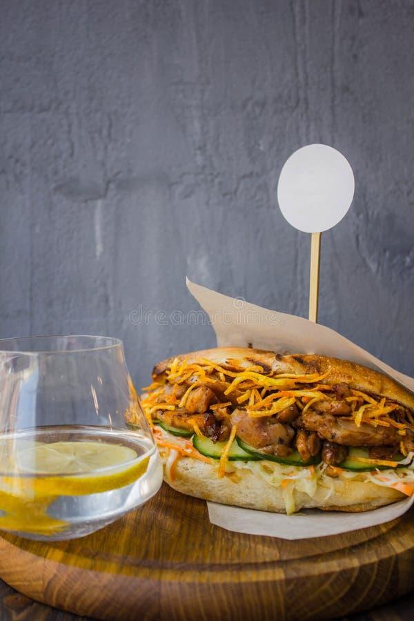 Sandwich avec le poulet et eau avec le citron images libres de droits