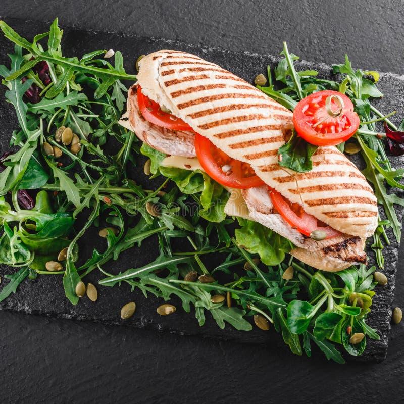 Sandwich avec le poulet, les l?gumes frais, le fromage et les verts grill?s par filet sur le panneau de schiste noir au-dessus du photographie stock