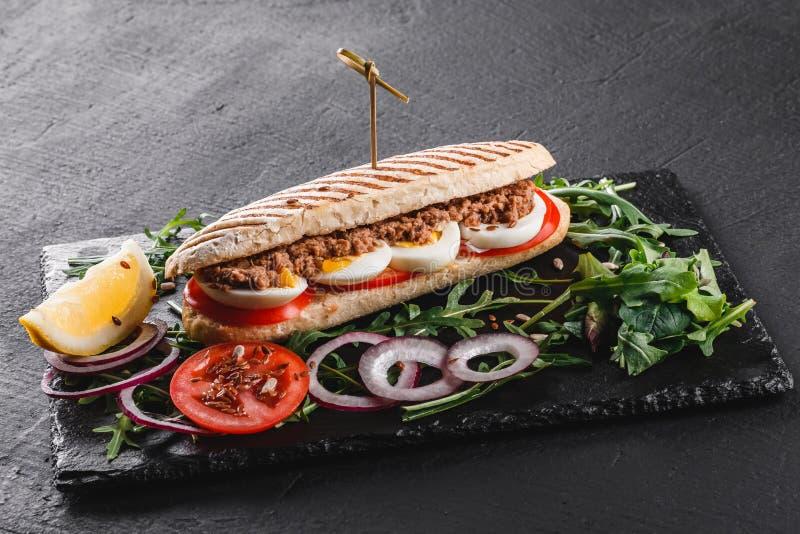 Sandwich avec le thon, les oeufs, les l?gumes frais et les verts sur le panneau de schiste noir au-dessus du fond en pierre noir  photographie stock libre de droits