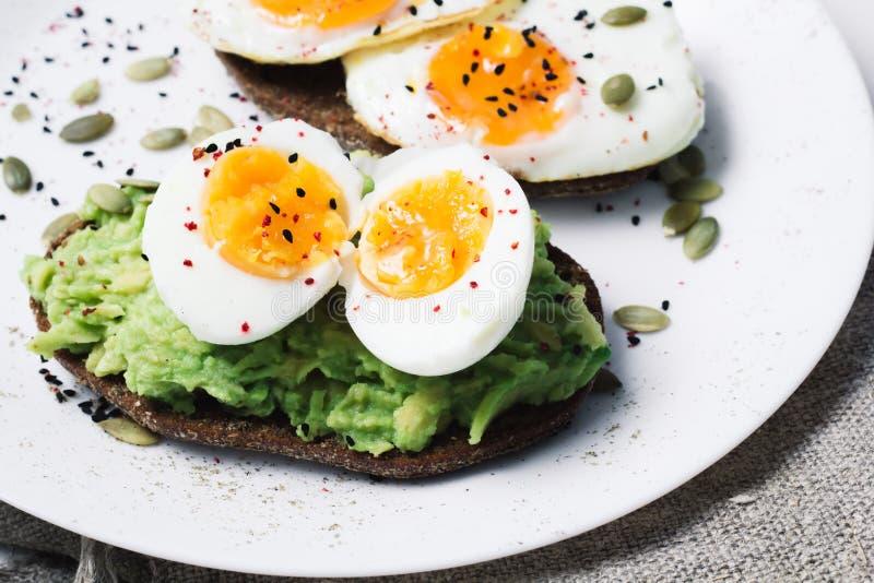 Sandwich avec les légumes frais, l'avocat, les oeufs durs et les graines de citrouille avec l'huile et le pain d'olive Alimentati images libres de droits