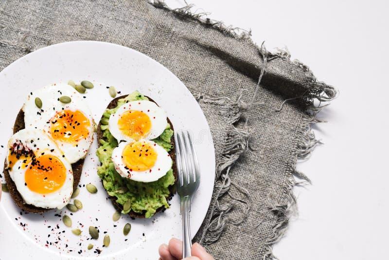 Sandwich avec les légumes frais, l'avocat, les oeufs durs et les graines de citrouille avec l'huile et le pain d'olive Alimentati images stock