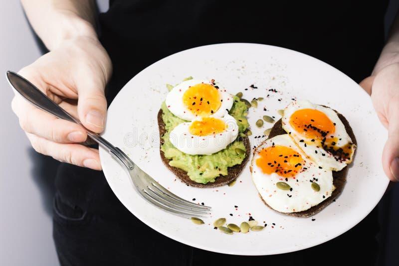 Sandwich avec les légumes frais, l'avocat, les oeufs durs et les graines de citrouille avec l'huile et le pain d'olive Alimentati photos libres de droits
