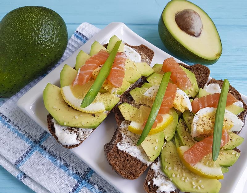 Sandwich bread healthy avocado dinner red fish plate lunch lemon gourmet blue wooden appetizer rustic. Sandwich avocado bread healthy lemon red fish rustic on royalty free stock images