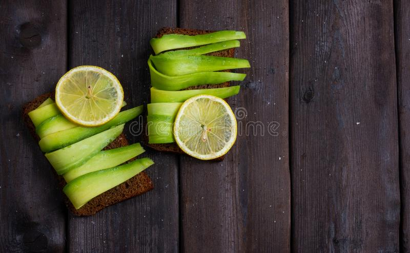 Sandwich with avocado on wooden background stock image