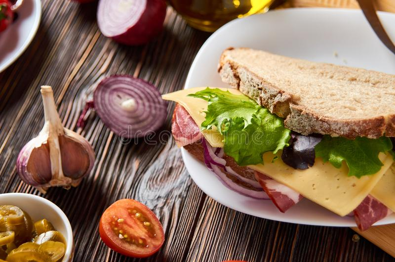 Sandwich with bacon, cheese, garlic, jalapeno pepper and herbs on a plate. On a wooden background stock photography