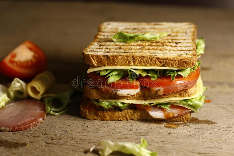 Sandwich with bacon, salad, cheese and tomato stock photography