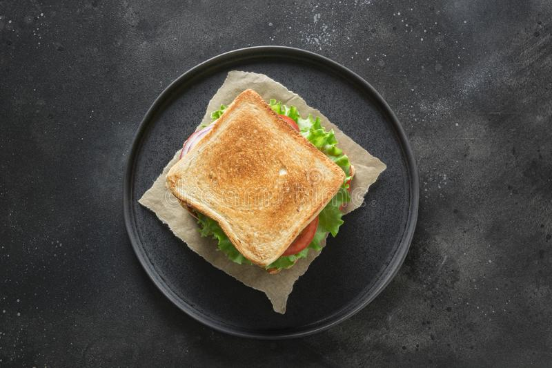 Sandwich with bacon, tomato, onion, salad on black background. Isolated. View from above royalty free stock image