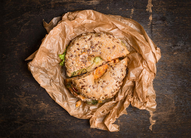 Sandwich on a Bagel on crumpled wrapping paper on rustic wooden background,top view royalty free stock photography