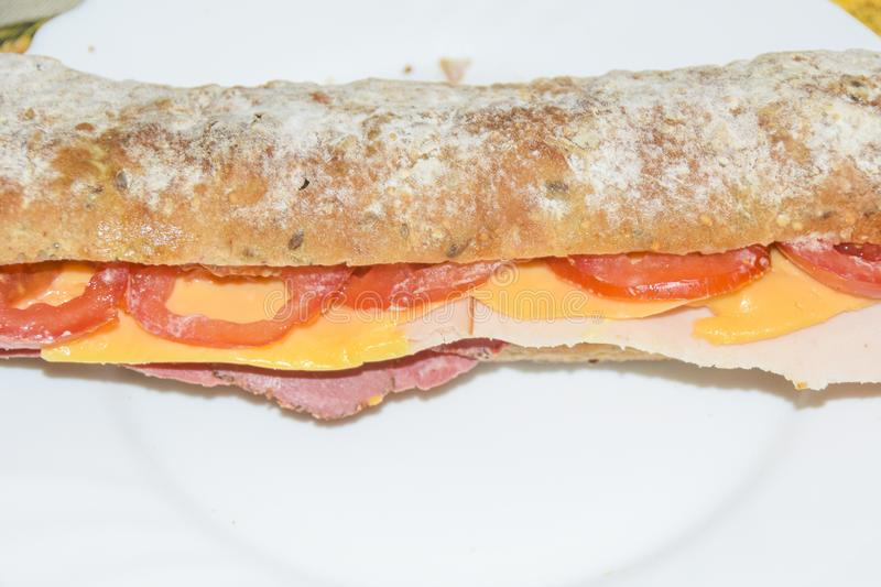 Sandwich in a baguette with ham, cheese, chicken and tomato. On a white plate stock image