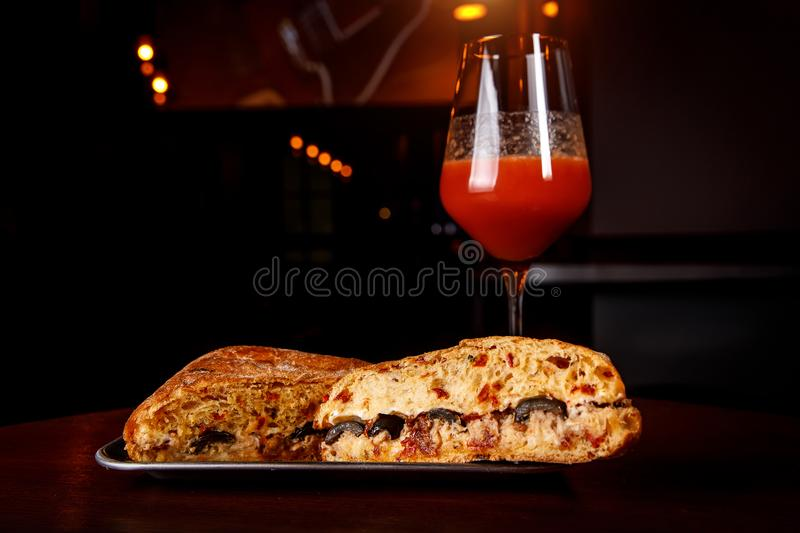 Sandwich in a bar on a wooden table. A tulip glass of beer on the background. royalty free stock photos