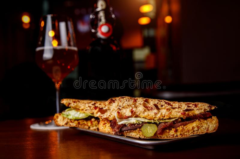 Sandwich in a bar on a wooden table. A tulip glass of beer on the background. stock images