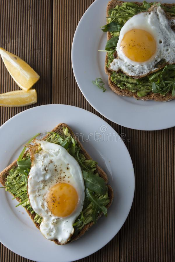 Sandwich or bread toast with avocado and a fried egg on a white plate on rustic wood table. Healthy food. Healthy eating royalty free stock images