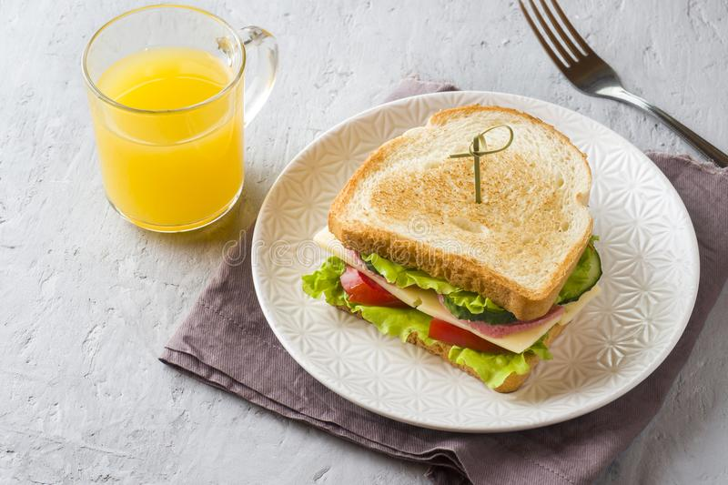 Sandwich with cheese, ham and fresh vegetables on a plate. Fresh juice and a Cup of coffee. The concept of Breakfast. royalty free stock images