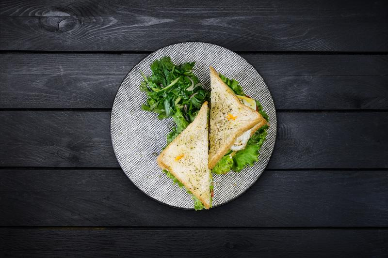 Sandwich with chicken and vegetables on a ceramic plate. On black wooden background, top view royalty free stock photo