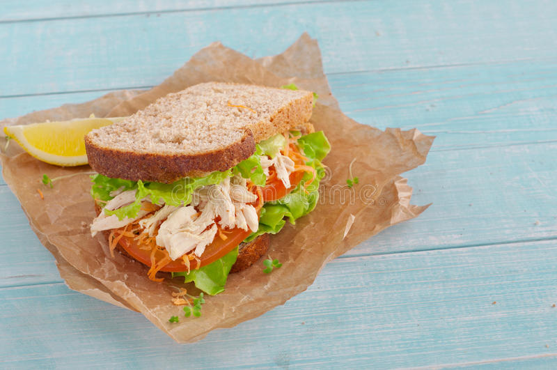 Sandwich with chicken on a wooden background royalty free stock image