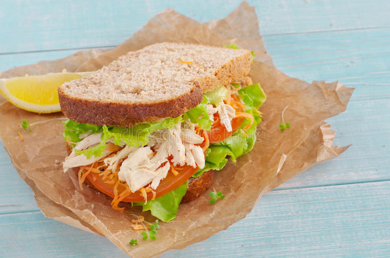 Sandwich with chicken on a wooden background. Sandwich with chicken on a paper on the blue wooden background. top view with copy space stock image