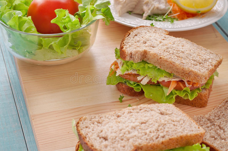 Sandwich with chicken on a wooden board stock photography