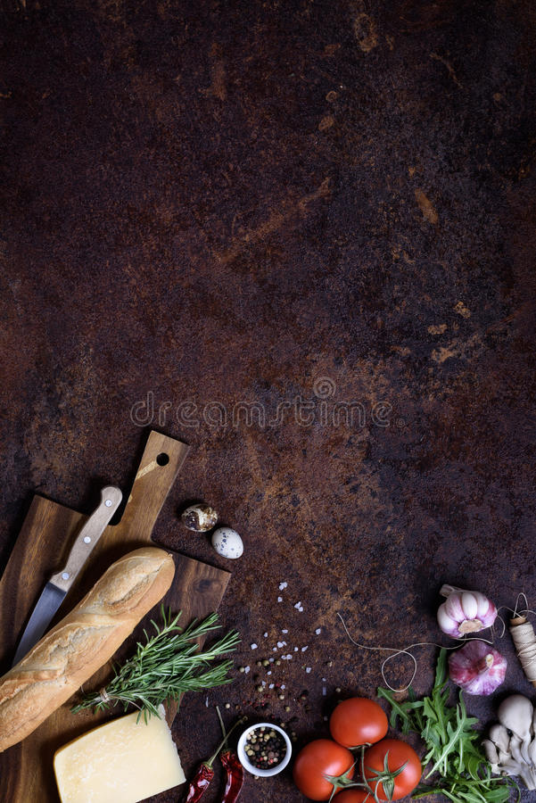 Sandwich cooking ingredients. French baguette with cheese and vegetables over rustic counter top. View above, copy space. royalty free stock photo
