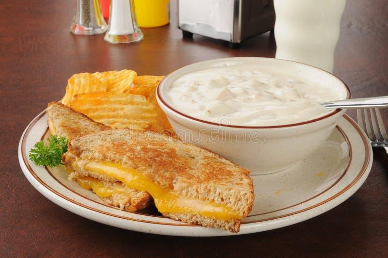 Sandwich cotto del formaggio con zuppa di molluschi e latte fotografia stock