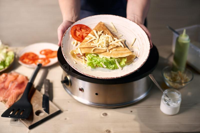 Sandwich crepe rolled up with vegetables and serving in white plate. Traditional hot breakfast food. Close up view. stock photos