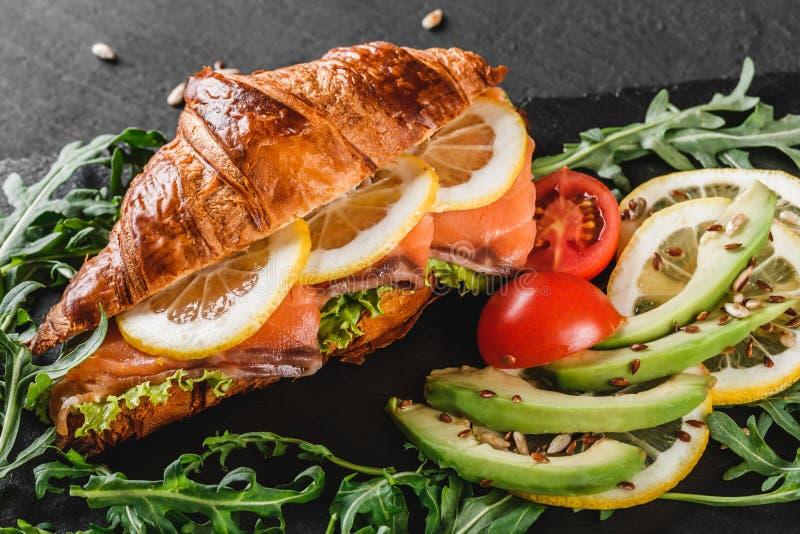 Sandwich ? croissant avec les poissons rouges, l'avocat, les l?gumes frais et l'arugula sur le panneau de schiste noir au-dessus  photos libres de droits