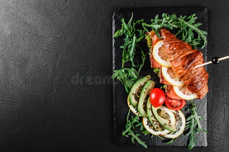 Sandwich ? croissant avec les poissons rouges, l'avocat, les l?gumes frais et l'arugula sur le panneau de schiste noir au-dessus  images libres de droits