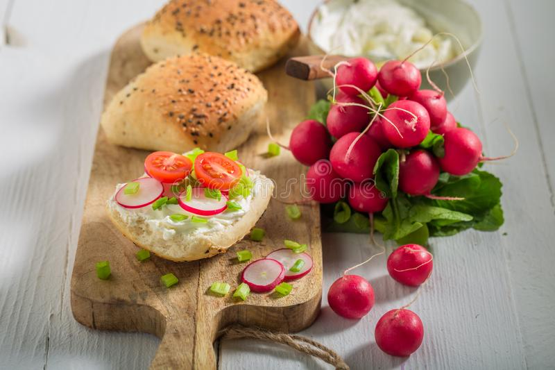 Sandwich with crunchy bread, fromage cheese and fresh radish. On wooden table royalty free stock image