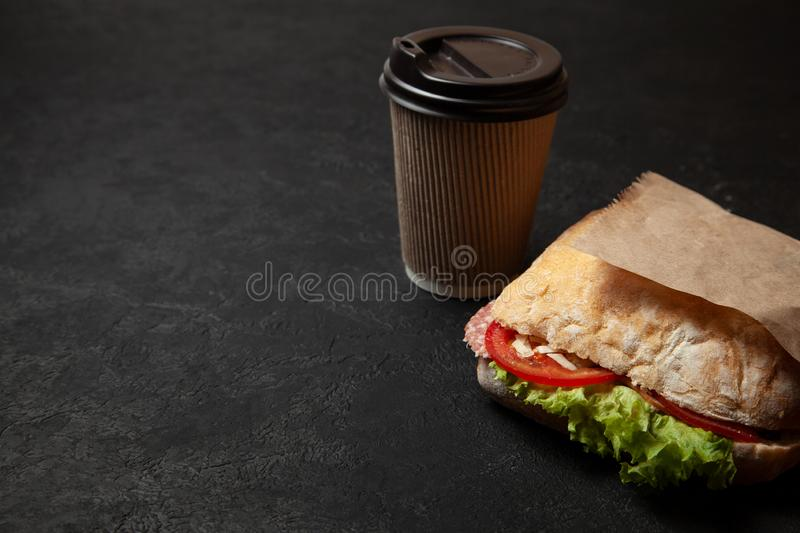 Sandwich and cup of coffee on black background. Morning breakfast or snack when hungry. Street food to go. Copy space for text. Sandwich and cup of coffee on stock image