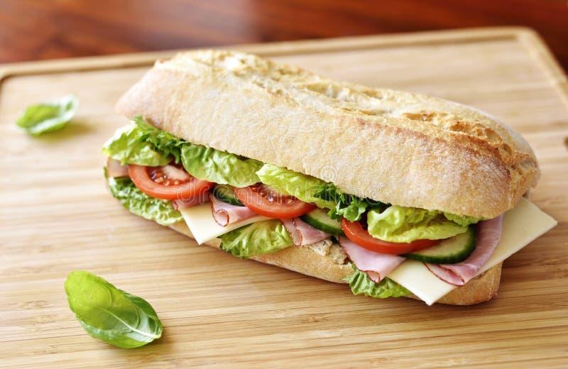 Sandwich délicieux à ciabatta avec du jambon, les tomates, la salade fraîche et le concombre photo libre de droits