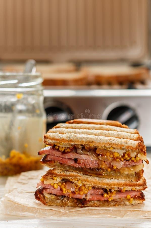 Sandwich délicieux avec de la viande, les oignons frits, le fromage et la moutarde sur le gril photos libres de droits