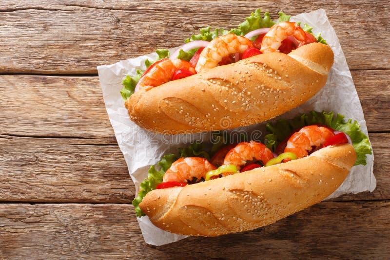 Sandwich délicieux avec des crevettes et des légumes frais en gros plan sur le parchemin vue sup?rieure horizontale image stock
