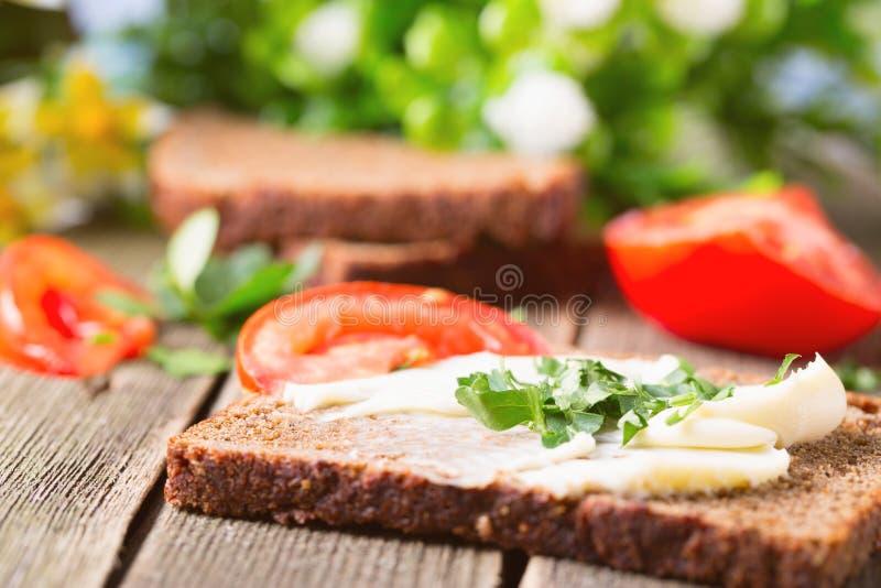 Sandwich de pain de seigle avec de l'huile, des verts et des tomates images libres de droits