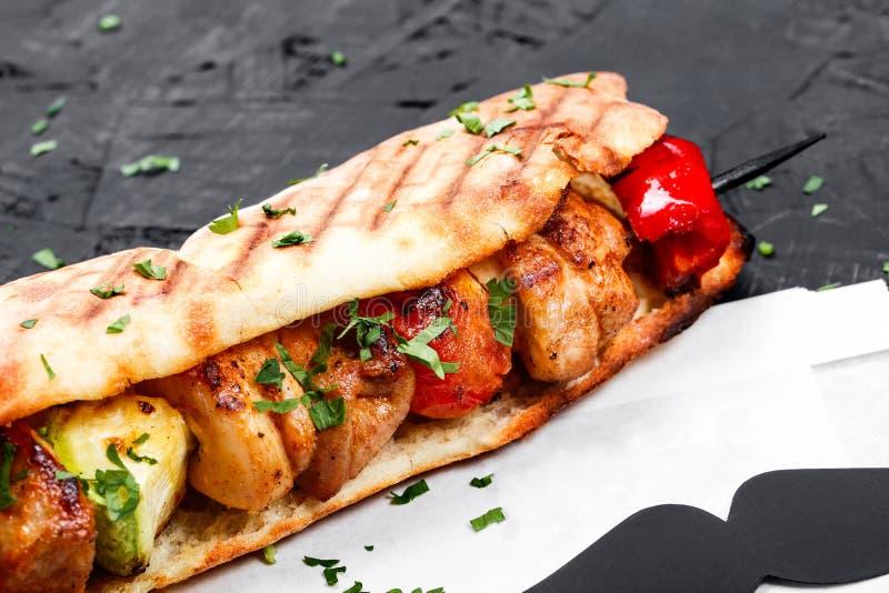 Sandwich de pain pita frais avec le poulet et les légumes grillés par filet sur le fond en bois foncé images libres de droits
