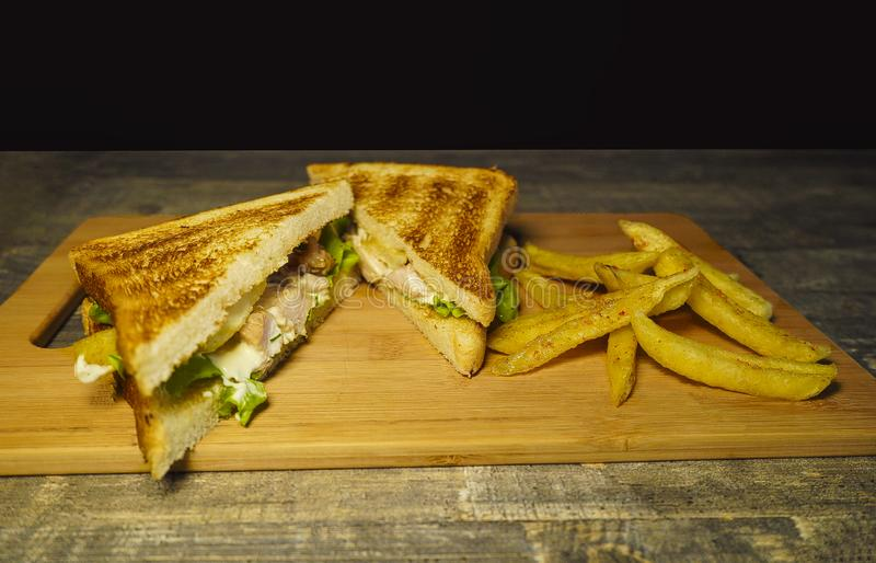 Sandwich des k?rzlich gemachten Roastbeefs und des Schweizer K?ses auf einem Schneidebrett lizenzfreie stockfotos