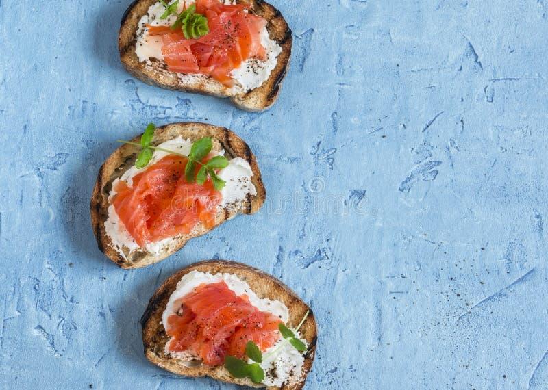 Sandwich des Lachs- und Frischkäses Auf einem blauen Hintergrund Draufsicht stockbilder