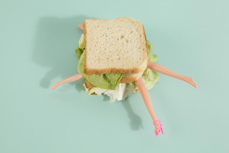 Sandwich doll. Parts of a doll`s body in a sandwich with salad and soft bread on a minimal background color. pop fun and quirky cannibalism stock photos