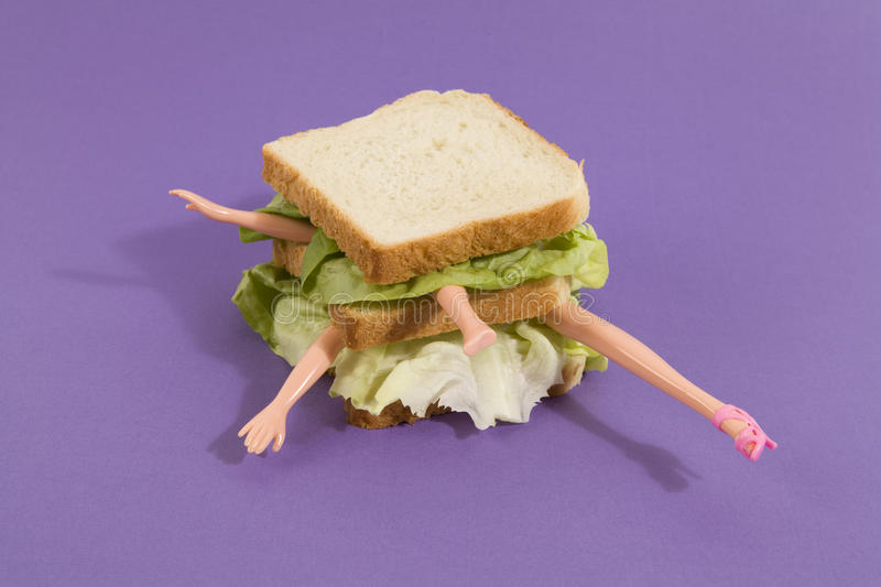 Sandwich doll. Parts of a doll`s body in a sandwich with salad and soft bread on a minimal background color. pop fun and quirky cannibalism royalty free stock photo