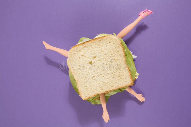Sandwich doll. Parts of a doll`s body in a sandwich with salad and soft bread on a minimal background color. pop fun and quirky cannibalism stock photo