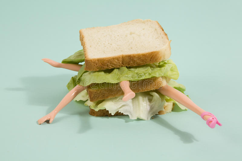 Sandwich doll. Parts of a doll`s body in a sandwich with salad and soft bread on a minimal background color. pop fun and quirky cannibalism royalty free stock images