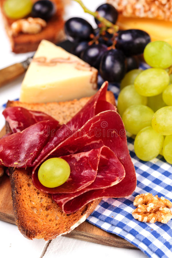 Sandwich with dried meet. Sandwich with b�ndnerfleisch - dried beef with variety of cheese and grapes on a cutting board stock images